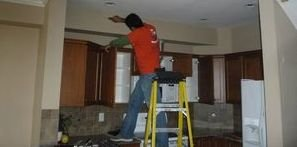 Technician Cleaning Water Logged Ceiling